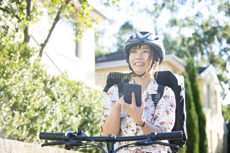 自転車にまたがってスマホを触っている配達員女性の写真素材 [FYI04540205]