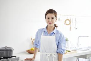 キッチンに立つカメラ目線の女性の写真素材 [FYI04540217]