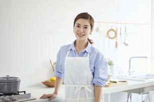 キッチンに立つカメラ目線の女性の写真素材 [FYI04540218]