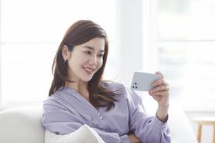 スマートフォンを見ながらソファでくつろぐ女性の写真素材 [FYI04540223]