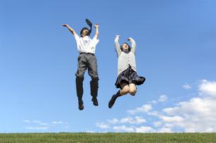 青空を背景にジャンプをする男女高校生の写真素材 [FYI04540734]