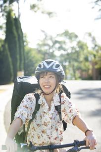 自転車に乗ってフードデリバリー をしている配達員女性の写真素材 [FYI04540761]
