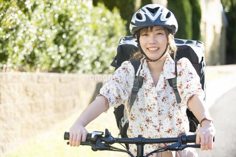 自転車に乗ってフードデリバリー をしている配達員女性の写真素材 [FYI04540762]
