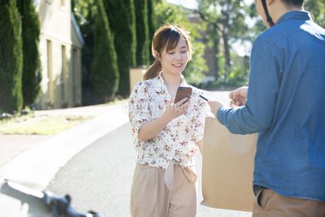 デリバリーの商品を受け取っている女性の写真素材 [FYI04540767]