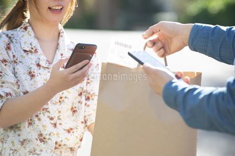 デリバリーの商品を受け取っている女性の写真素材 [FYI04540769]