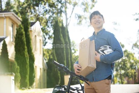 紙袋とヘルメットを抱えている笑顔の配達員の写真素材 [FYI04540772]