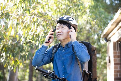 ヘルメットを装着しているフードデリバリー配達員男性の写真素材 [FYI04540799]