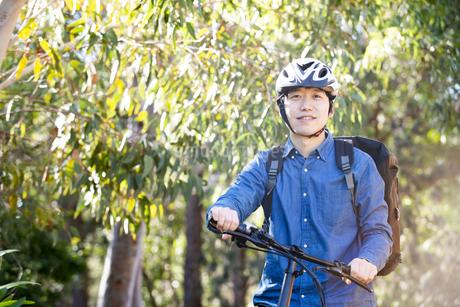 自転車に乗っているるフードデリバリー配達員男性の写真素材 [FYI04540814]