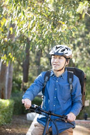 自転車に乗っているるフードデリバリー配達員男性の写真素材 [FYI04540817]
