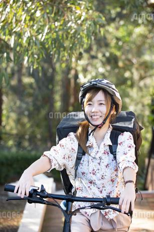 自転車に乗っているるフードデリバリー配達員女性の写真素材 [FYI04540818]