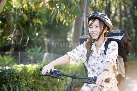 自転車に乗っているるフードデリバリー配達員女性の写真素材 [FYI04540820]