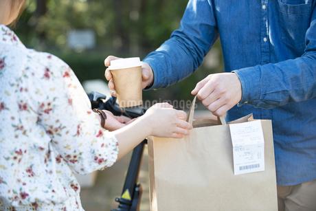 フードデリバリー の商品を受け渡ししている男女の手元の写真素材 [FYI04540826]