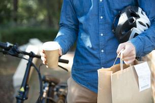 コーヒーカップと紙袋を持っているフードデリバリー配達員の手元の写真素材 [FYI04540830]