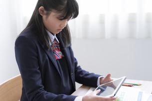 タブレットPCを使って勉強する女子学生の写真素材 [FYI04541136]