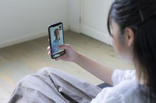スマートフォンで祖父とビデオ通話をする女の子の写真素材 [FYI04541152]