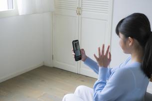スマートフォンで祖父とビデオ通話をする女の子の写真素材 [FYI04541153]