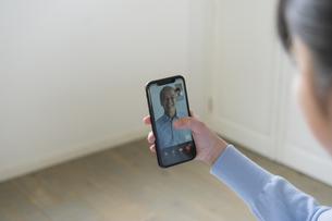 スマートフォンで祖父とビデオ通話をする女の子の写真素材 [FYI04541154]