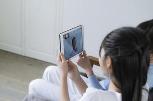 タブレットPCで祖父とビデオ通話をする女の子の写真素材 [FYI04541157]