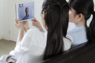 タブレットPCで祖父とビデオ通話をする女の子の写真素材 [FYI04541462]