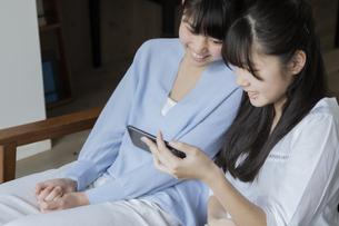 スマートフォンを見る女の子の写真素材 [FYI04541465]