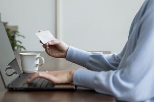 ノートパソコンでインターネット決済をする女性の手元の写真素材 [FYI04541468]