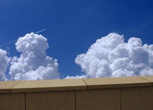 バルコニーから見る飛行機雲と入道雲の写真素材 [FYI04542732]