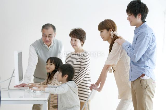 パソコンを使う子供たちを見守る家族の写真素材 [FYI04543310]