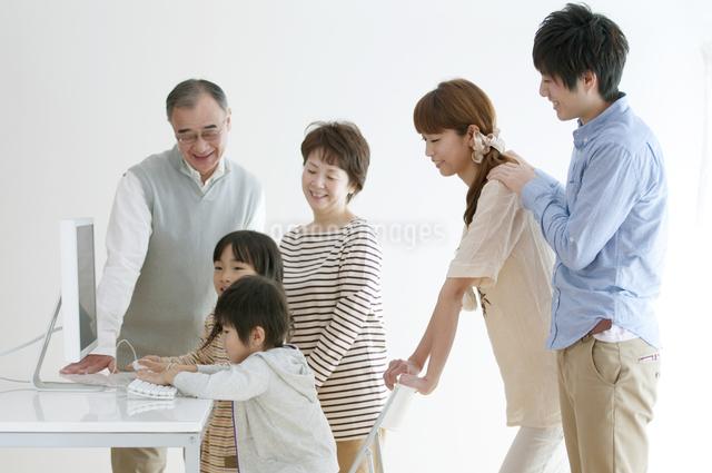 パソコンを使う子供たちを見守る家族の写真素材 [FYI04543311]