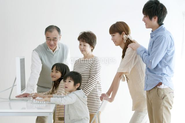 パソコンを使う子供たちを見守る家族の写真素材 [FYI04543312]