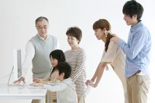 パソコンを使う子供たちを見守る家族の写真素材 [FYI04543313]