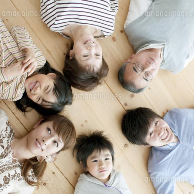 床に寝転ぶ3世代家族の写真素材 [FYI04543334]