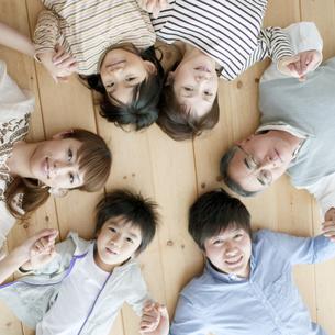 床に寝転ぶ3世代家族の写真素材 [FYI04543337]
