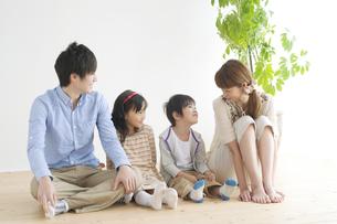 床に座る4人家族の写真素材 [FYI04543344]