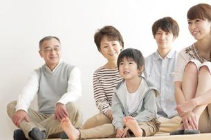 床に座り微笑む3世代家族の写真素材 [FYI04543404]