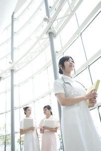 病院ロビーを歩く看護師の写真素材 [FYI04543473]