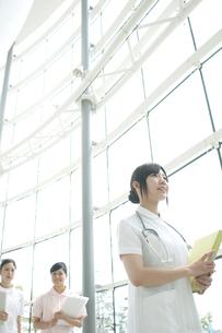 病院ロビーを歩く看護師の写真素材 [FYI04543474]