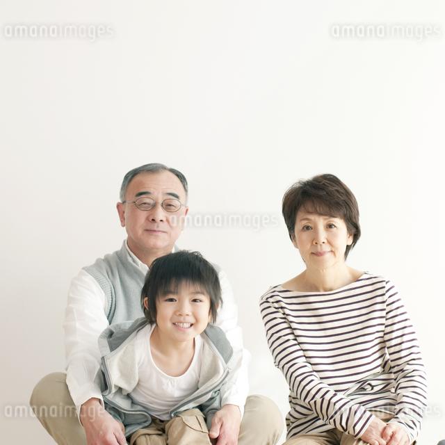 床に座り微笑む孫と祖父母の写真素材 [FYI04543642]