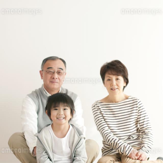床に座り微笑む孫と祖父母の写真素材 [FYI04543643]