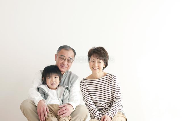 床に座り微笑む孫と祖父母の写真素材 [FYI04543644]