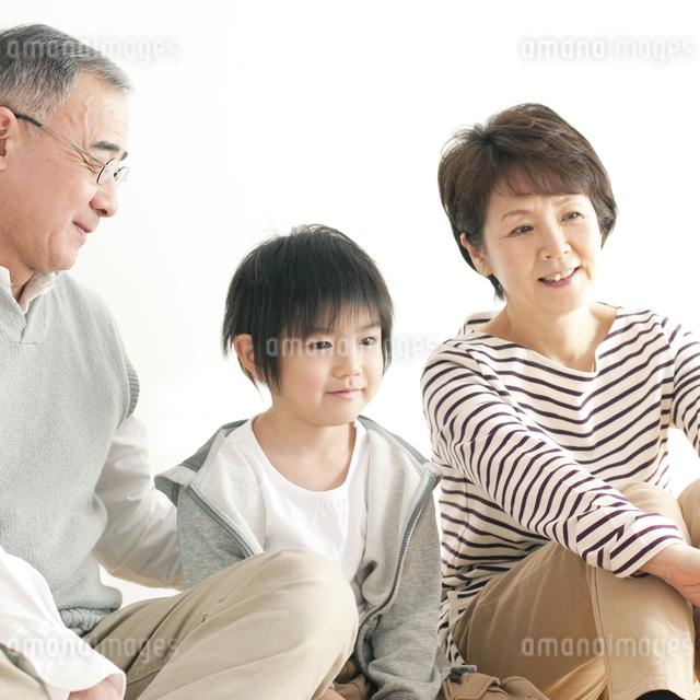 床に座り微笑む孫と祖父母の写真素材 [FYI04543645]