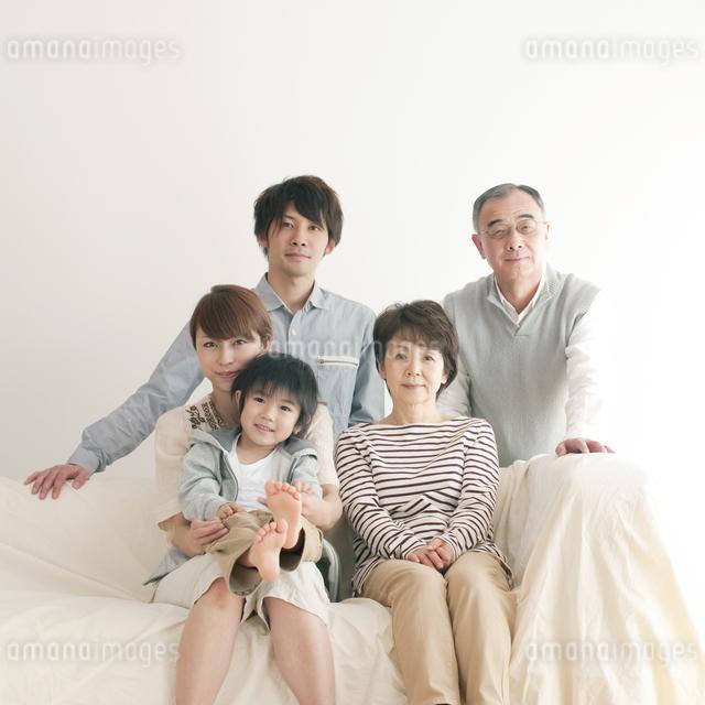 ソファーに座り微笑む3世代家族の写真素材 [FYI04543673]