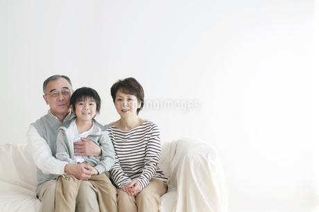 ソファーに座り微笑む孫と祖父母の写真素材 [FYI04543686]