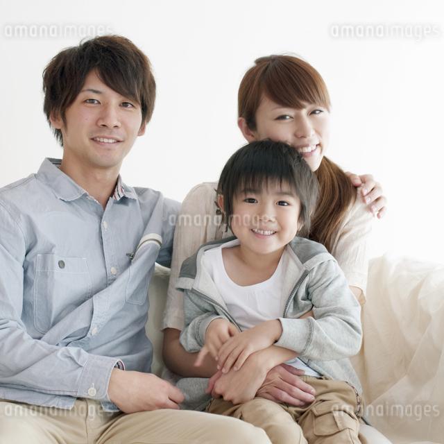 ソファーに座り微笑む家族の写真素材 [FYI04543690]