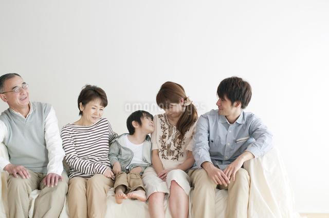ソファーに座り微笑む3世代家族の写真素材 [FYI04543704]
