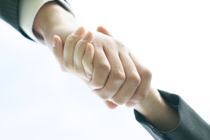 握手をするビジネスマンとビジネスウーマンの手元の写真素材 [FYI04543716]