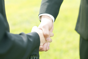 握手をするビジネスマンとビジネスウーマンの手元の写真素材 [FYI04543719]