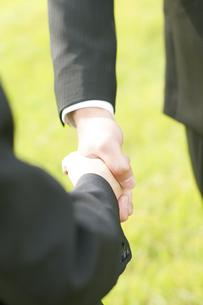握手をするビジネスマンとビジネスウーマンの手元の写真素材 [FYI04543720]