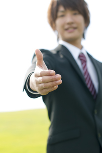 草原で手を差し出すビジネスマンの写真素材 [FYI04543732]