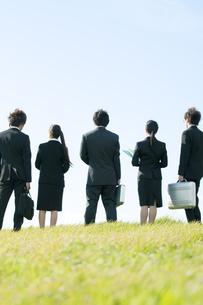 草原に立つビジネスマンとビジネスウーマンの後姿の写真素材 [FYI04543742]