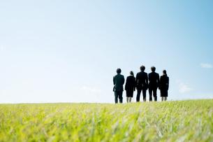 草原に立つビジネスマンとビジネスウーマンの後姿の写真素材 [FYI04543752]
